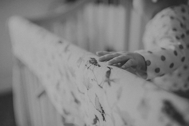 One year old baby girl fingers on top of crib