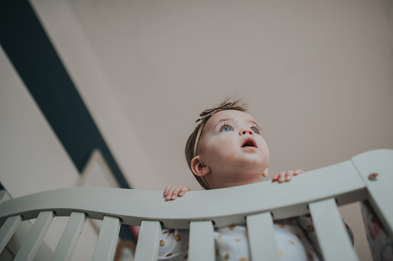 One year old baby girl in crib looking out the window