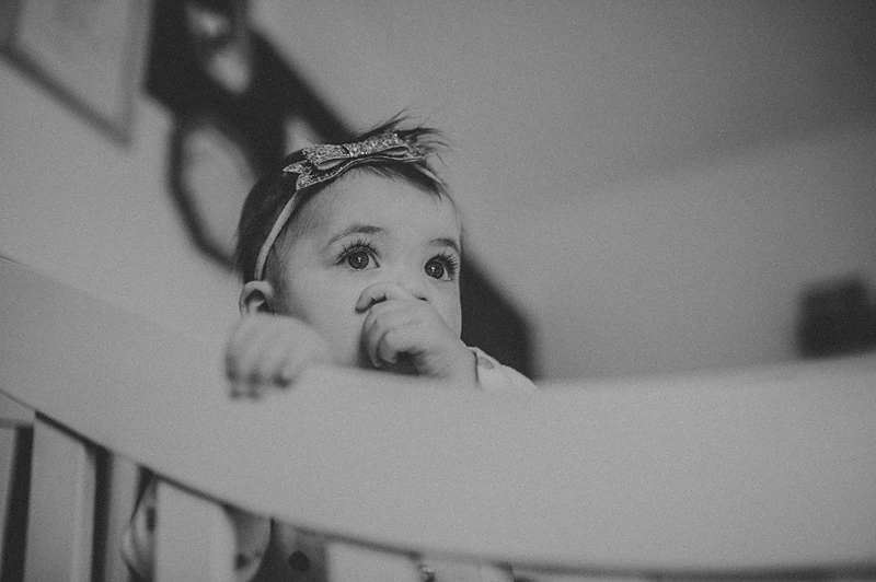 One year old baby girl sucking thumb in crib looking out window