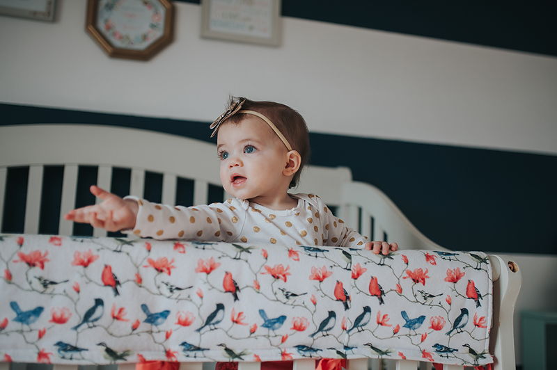 One year old baby girl in crib looking out window