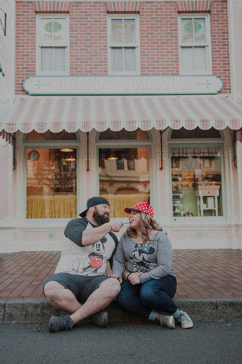 Couple eating churros and people watching on disneyland main street