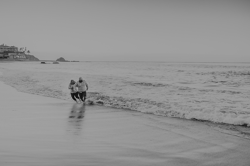 Couple running from the waves on beach at sunrise in California.