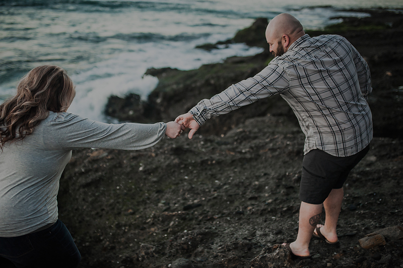Couple helping each other on rocky beach in California.