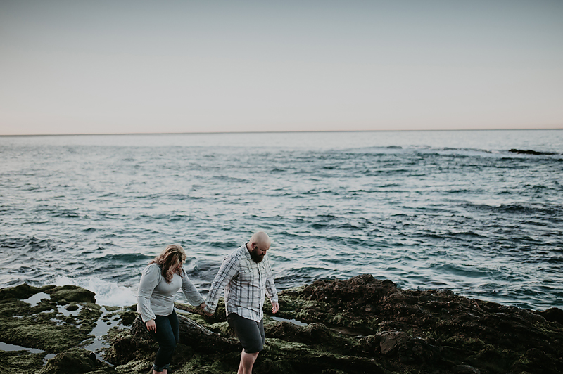 Couple walking hand in hand on mossy green rocks among the ocean.