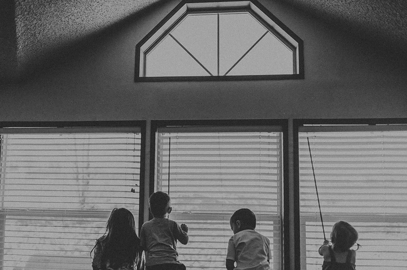 Little kids looking out windows together