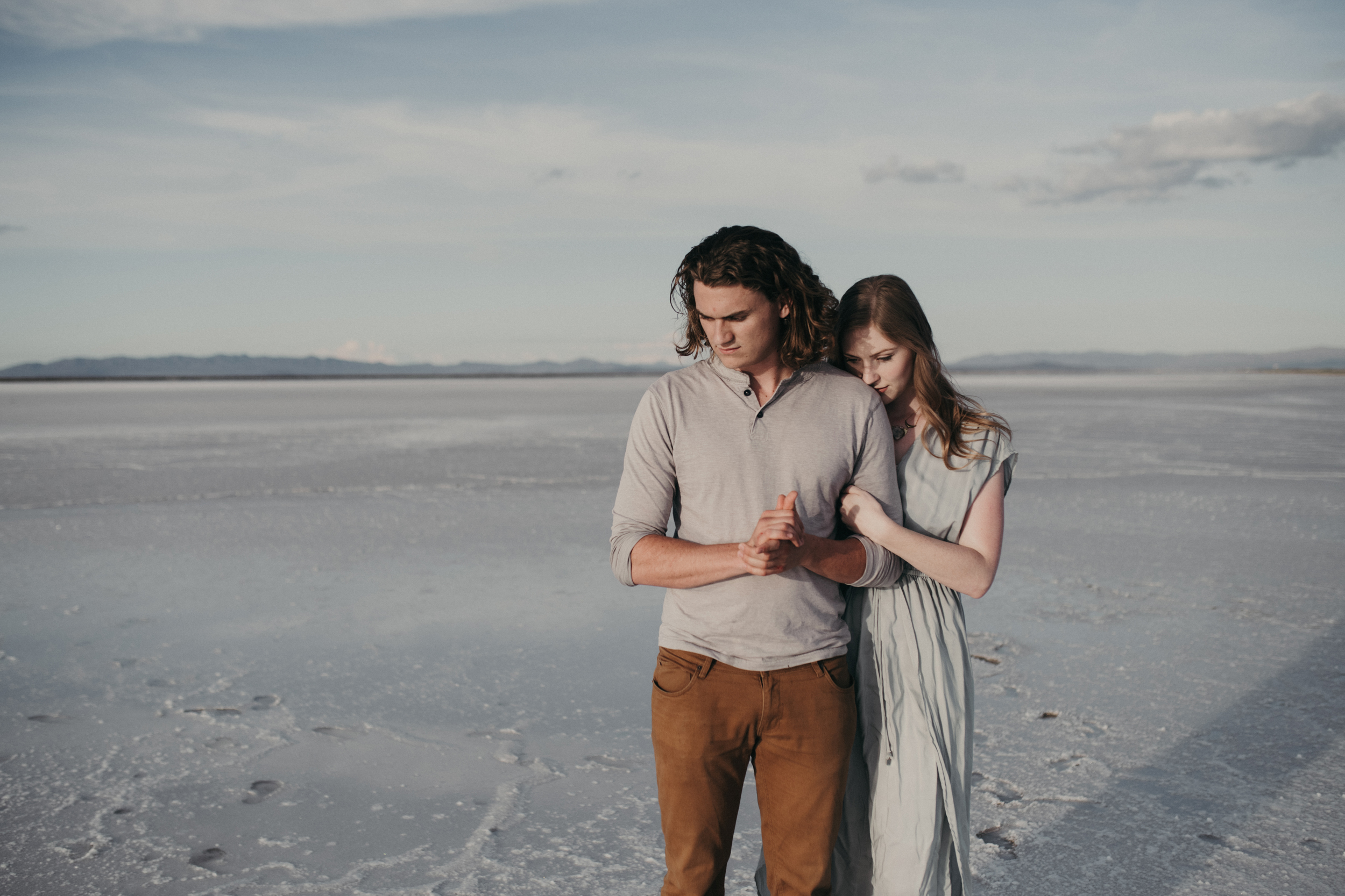 Girl hugging boy from behind on the salt flats