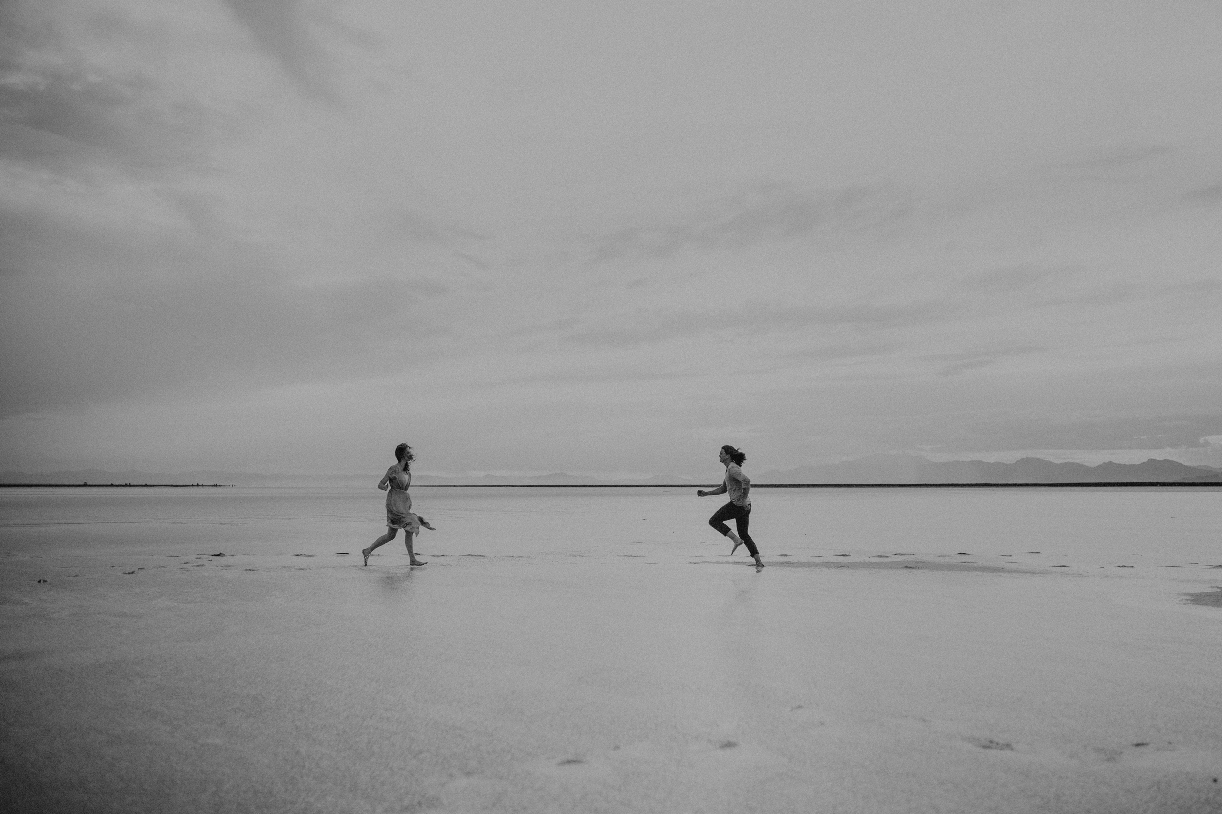 Couple running together on water and salt flats