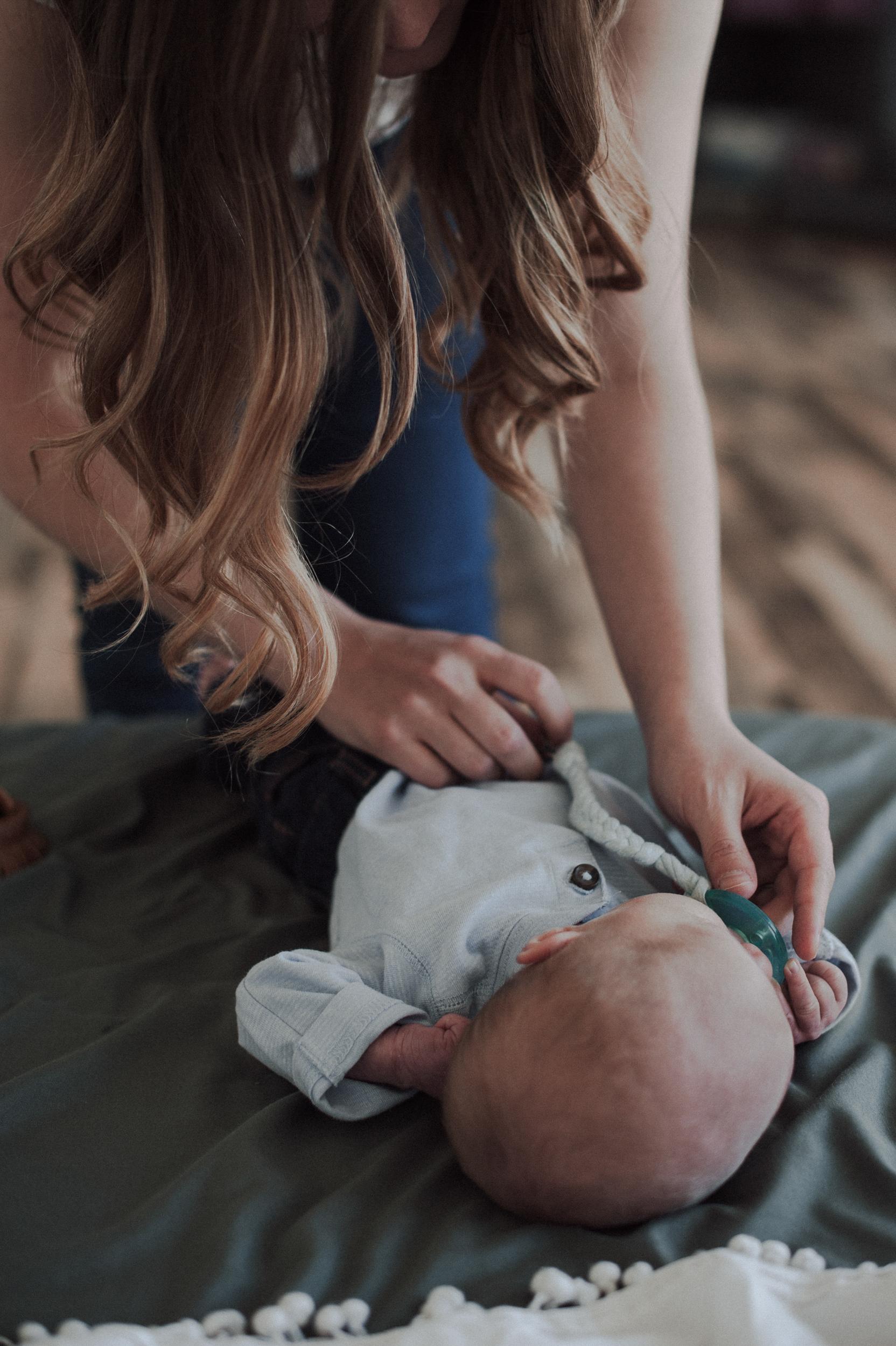 Mom dressing baby boy giving him binky