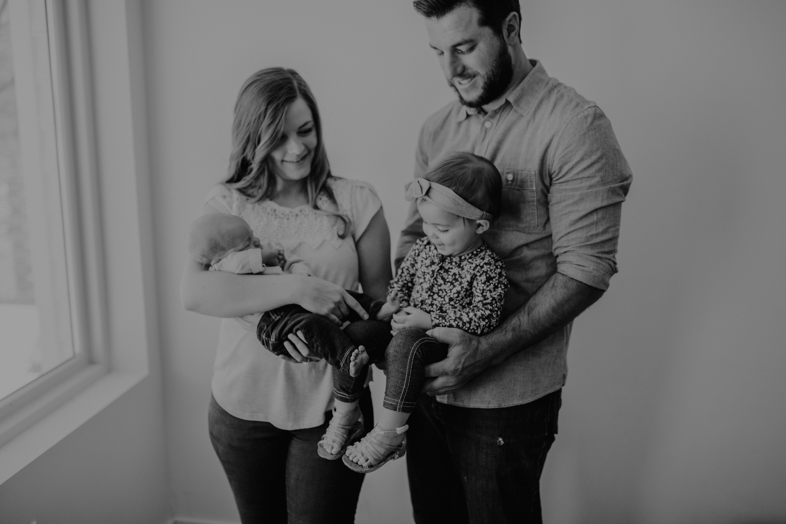 Mom and dad holding toddler girl and baby boy