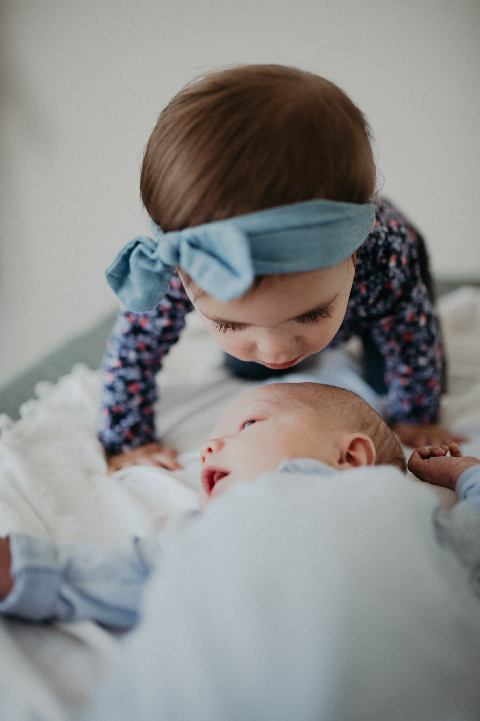 Toddler girl kissing baby brother