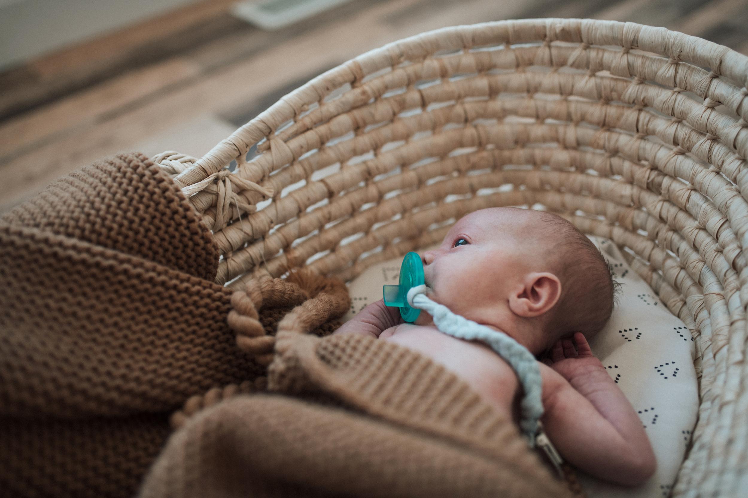Baby boy lying in Moses basket sucking on binky brown blanket