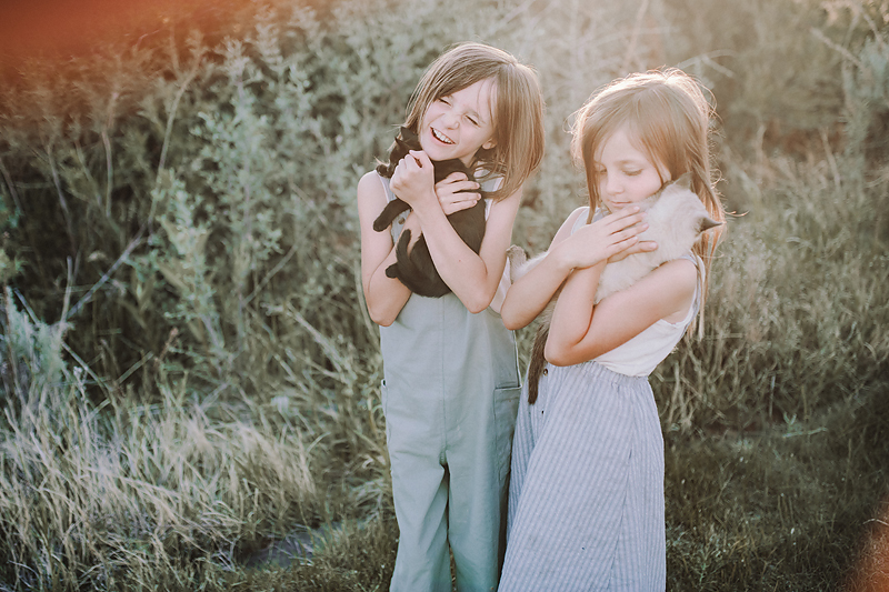 two girls holding kittens laughing in the sun