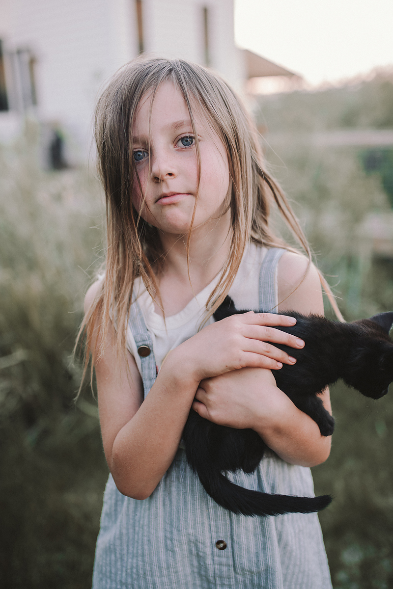 girl in dress holding black kitten