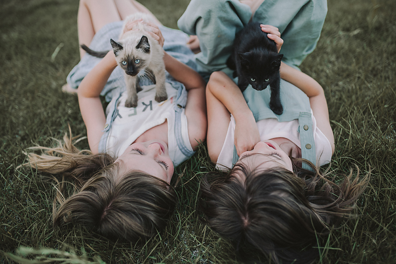 two girls lying on grass holding kittens