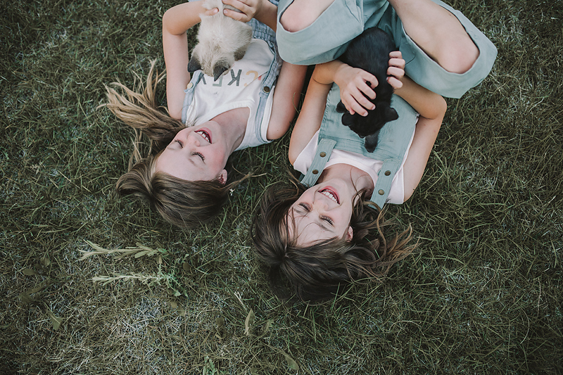 two girls lying on grass holding kittens laughing