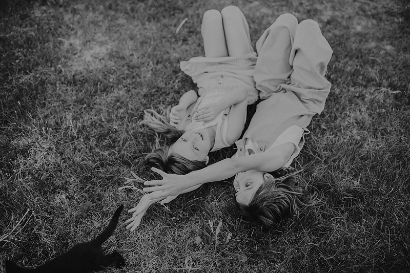 two girls lying on grass with kitten