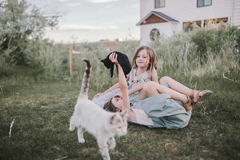 girls sitting on green grass with black kitten and white cat