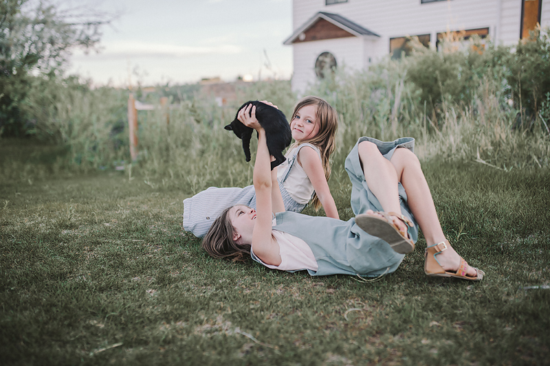 two girls lying on grass holding black kitten