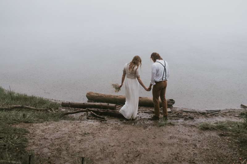 Couple in wedding gown and suspenders on lake