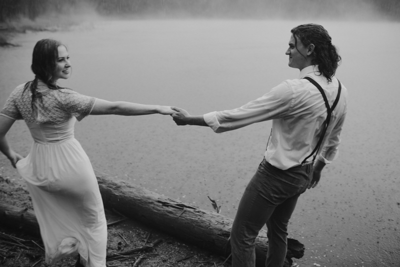 Couple holding hands in rain in front of foggy lake