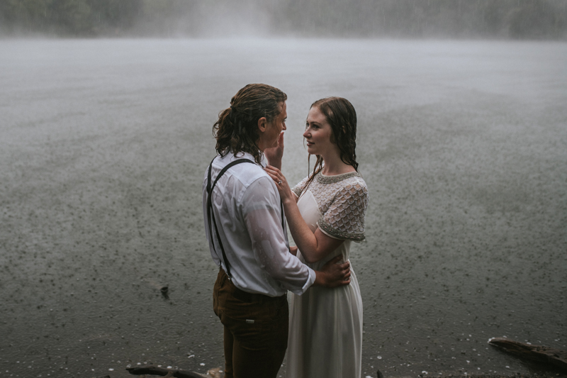 Couple in front of foggy lake in the rain