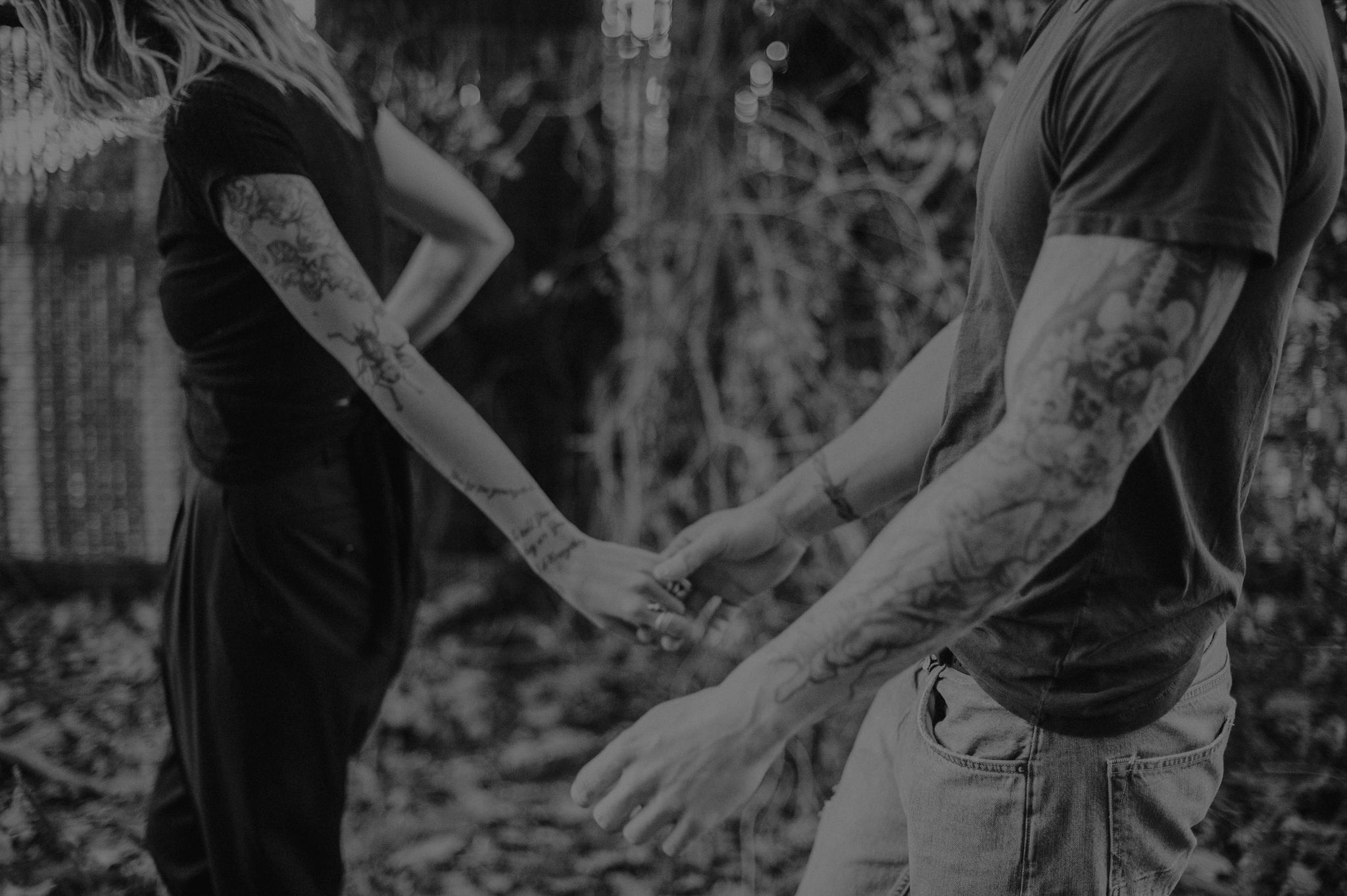 Tattooed couple holding hands walking outside