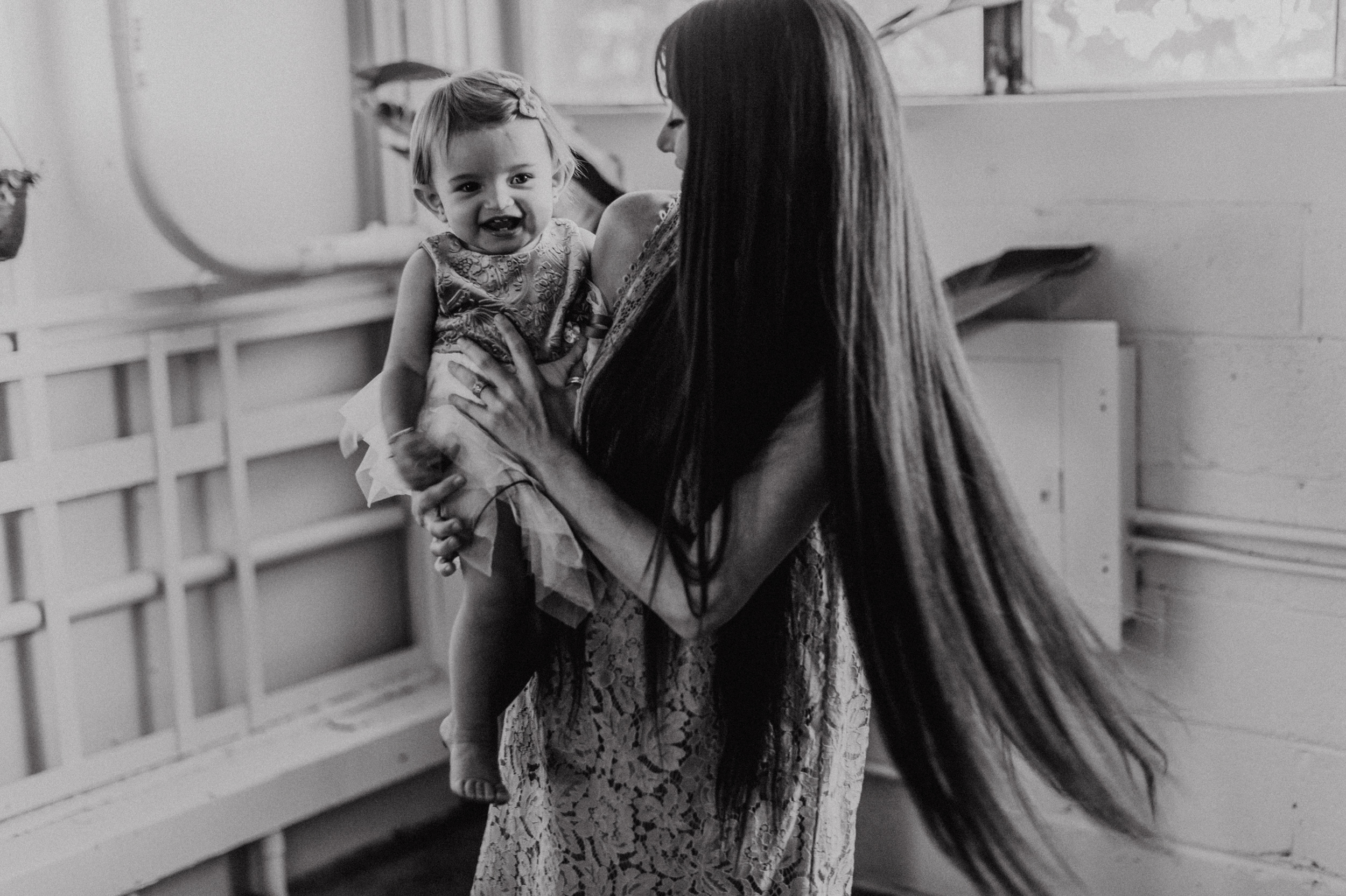 Mom with long hair spinning around with baby girl