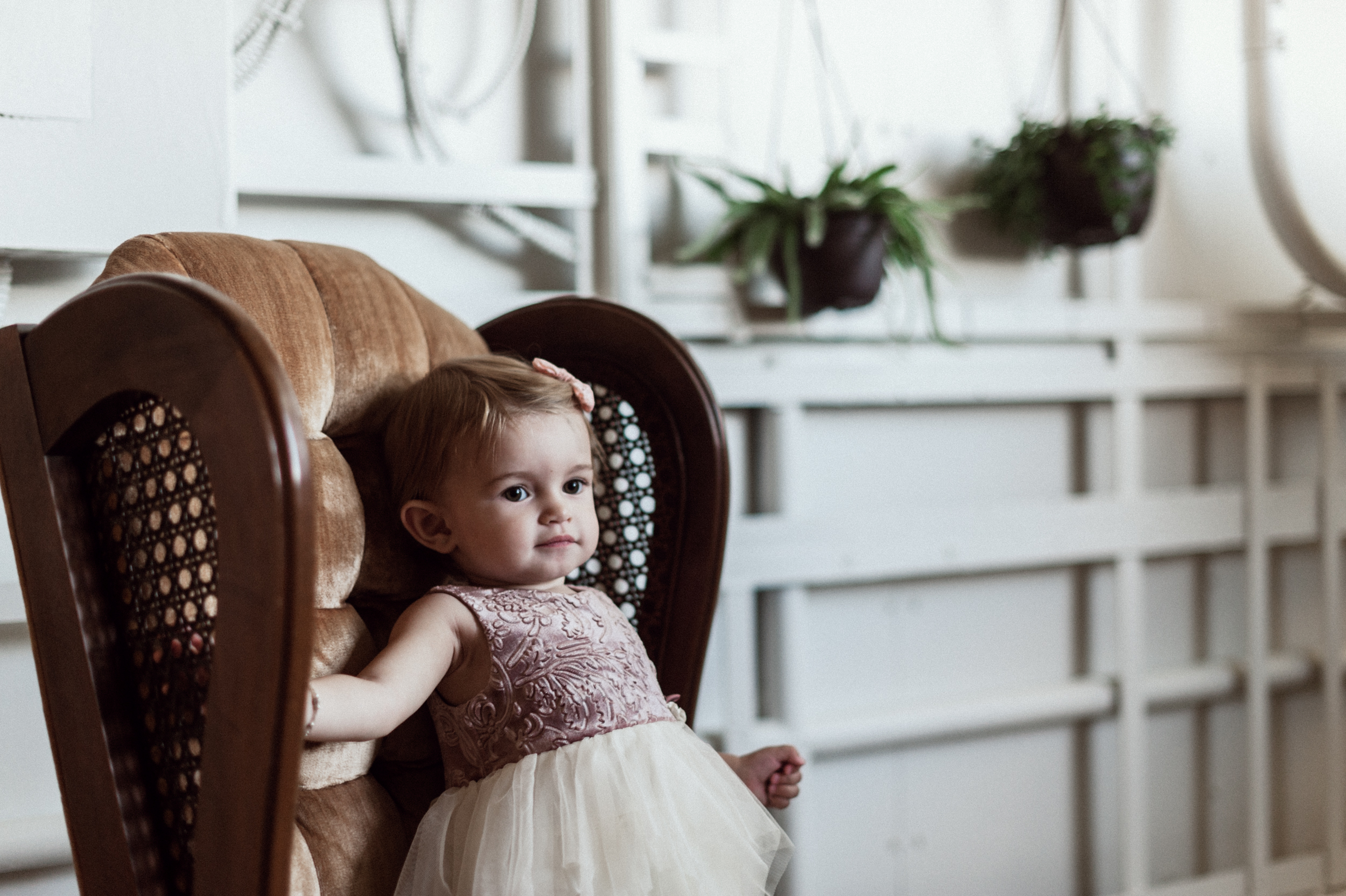 Baby girl in tutu dress sitting on brown chair
