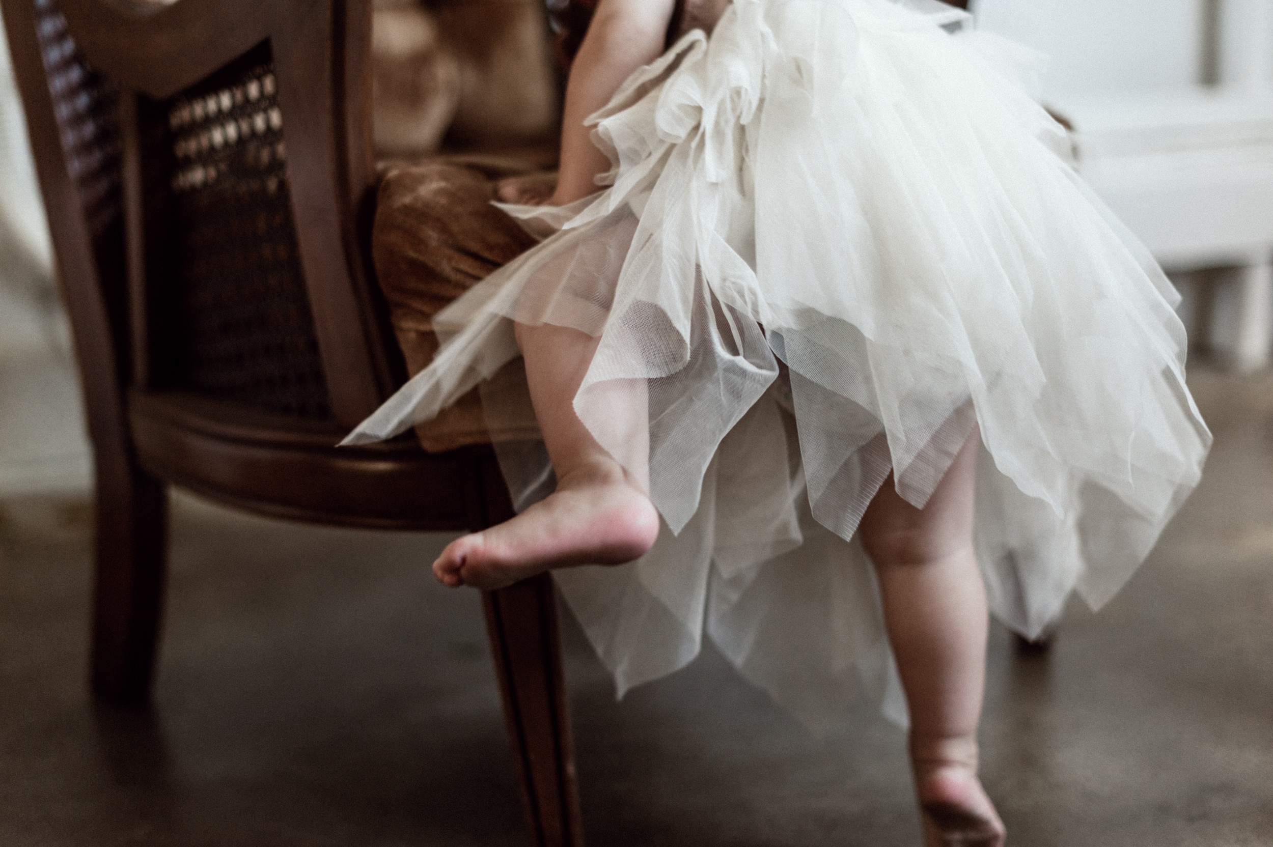 Baby girl in tutu dress climbing on velvet chair