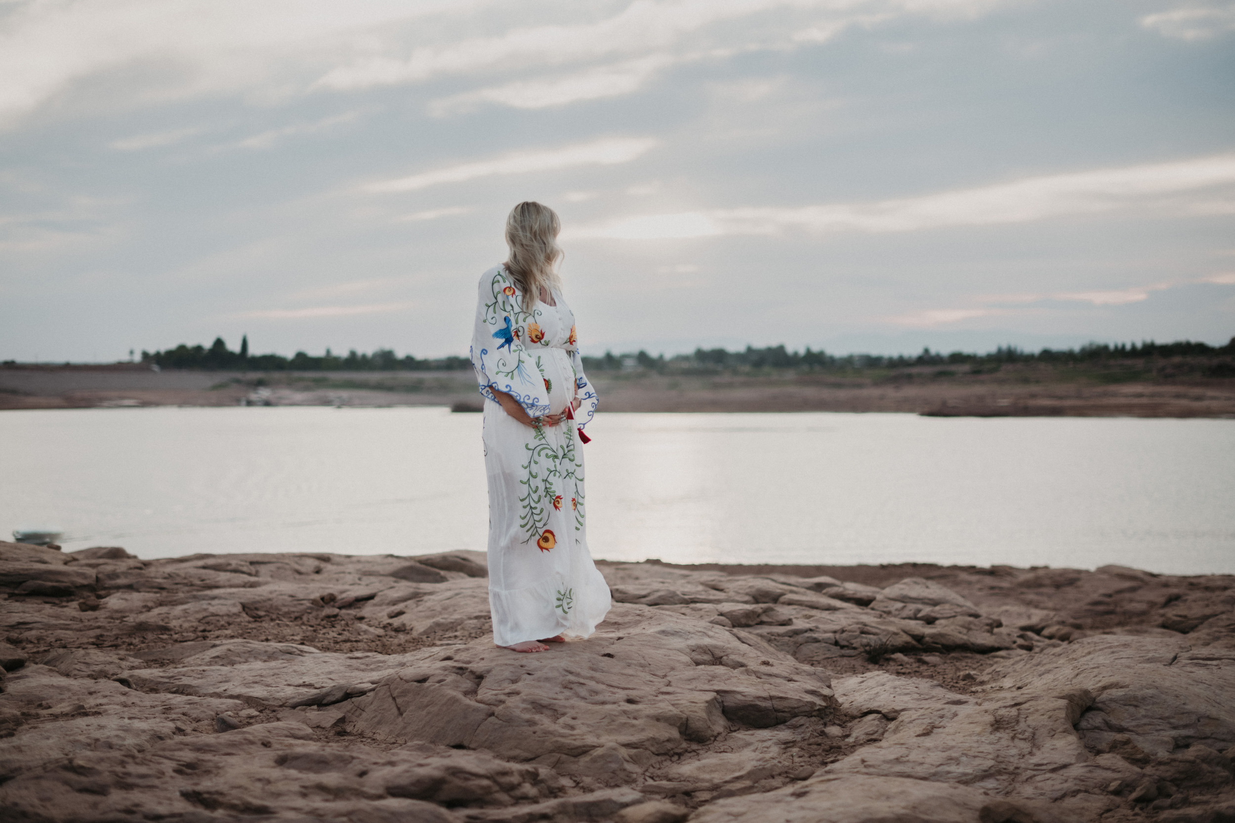 Pregnant woman in front of lake on rocks