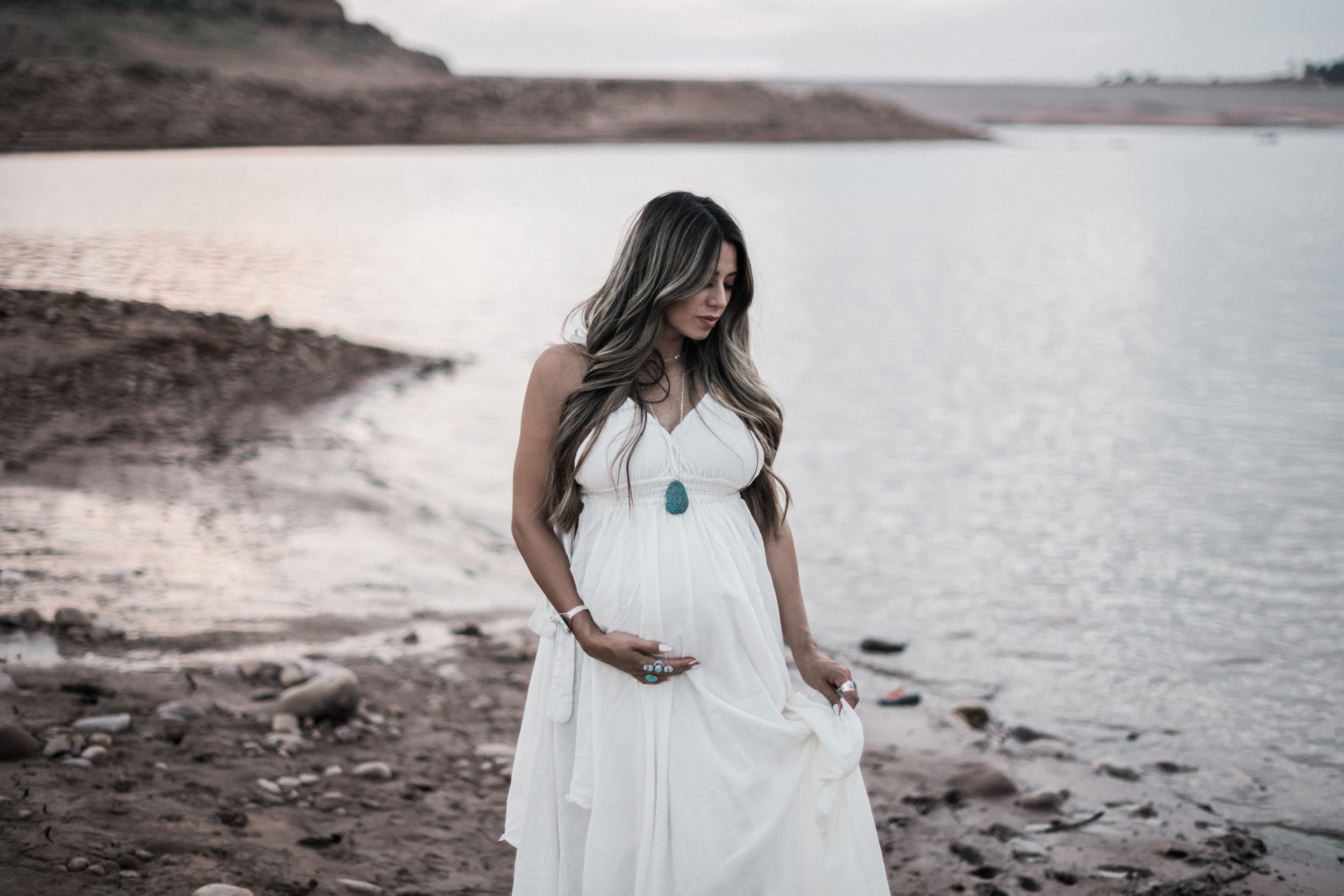 Pregnant woman on beach at lake turquoise necklace