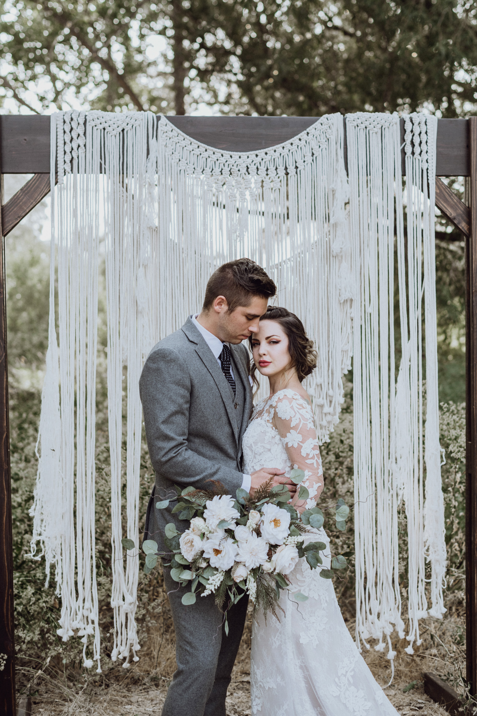 Groom holding bride in front of Macrame
