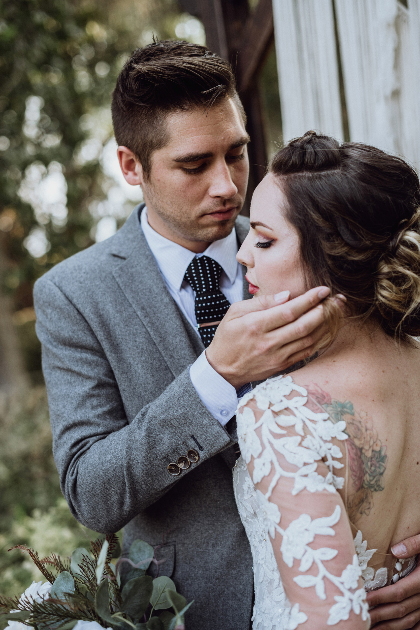 Groom touching brides face in front macrame