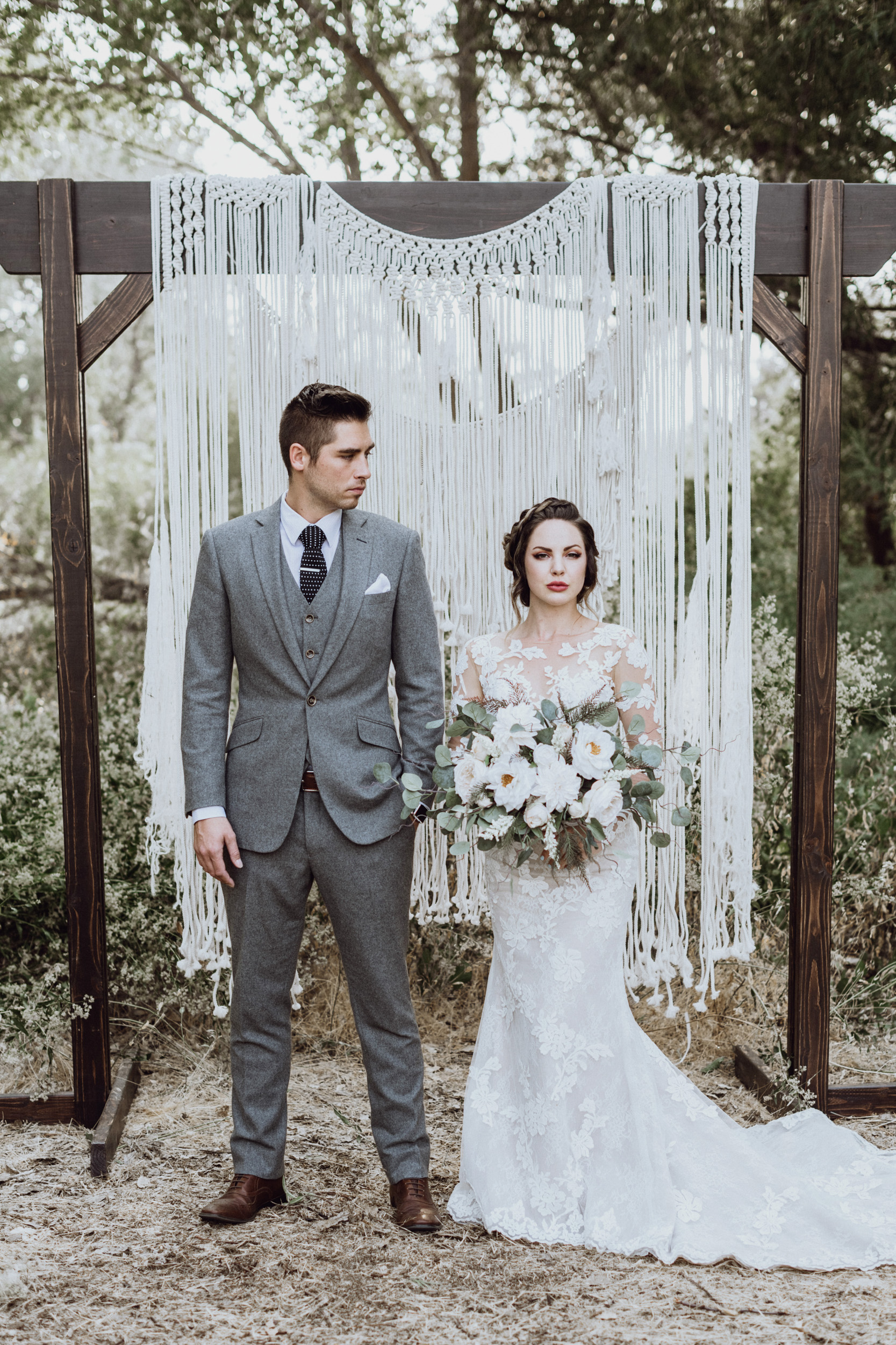 Bride holding bouquet with groom in front of macrame
