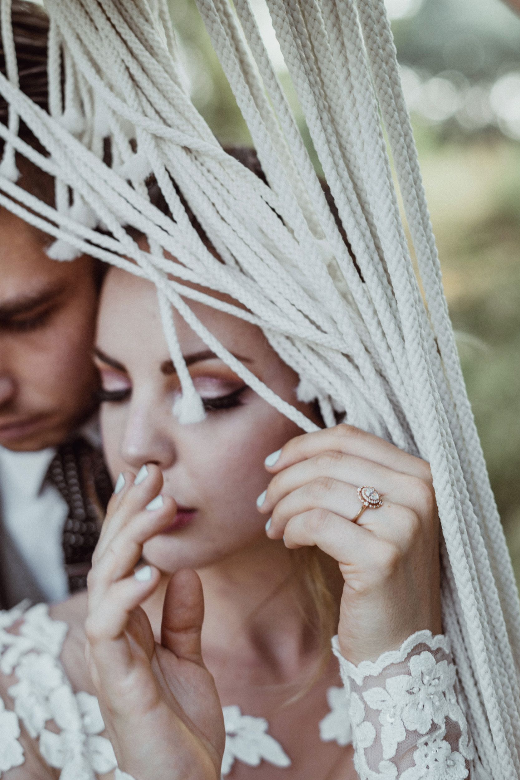 Bride wearing rose gold wedding ring in lace dress