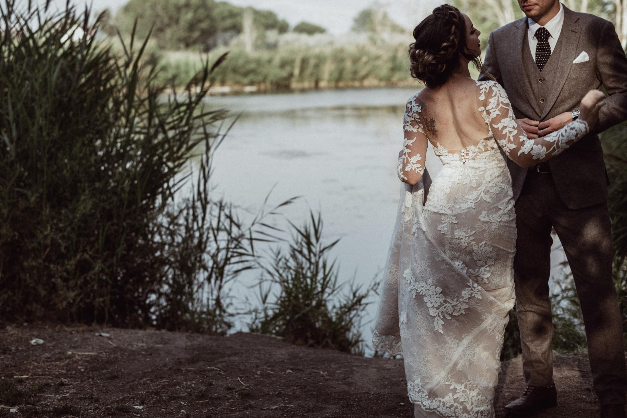 Bride and groom holding hands at loch lomond pond