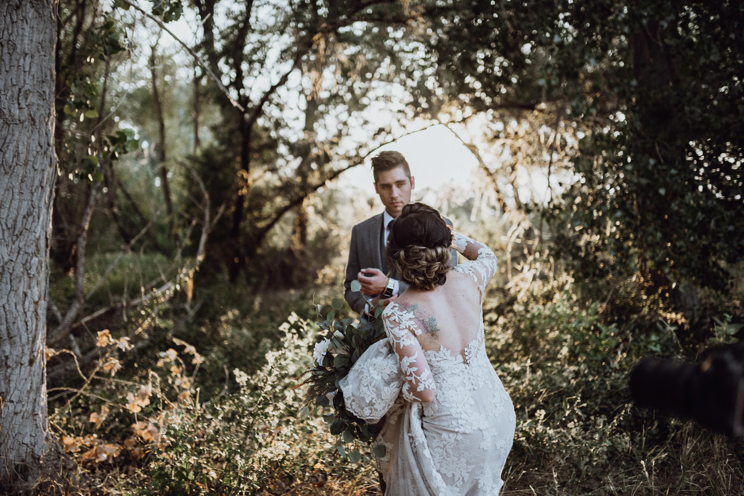 Bride walking towards groom in grassy field