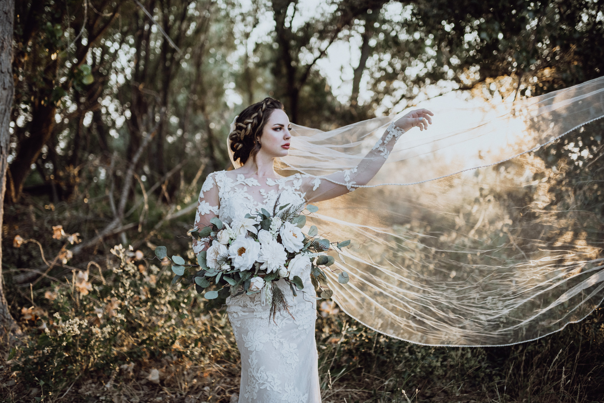 Bride holding bouquet in grassy field at Saratoga Springs