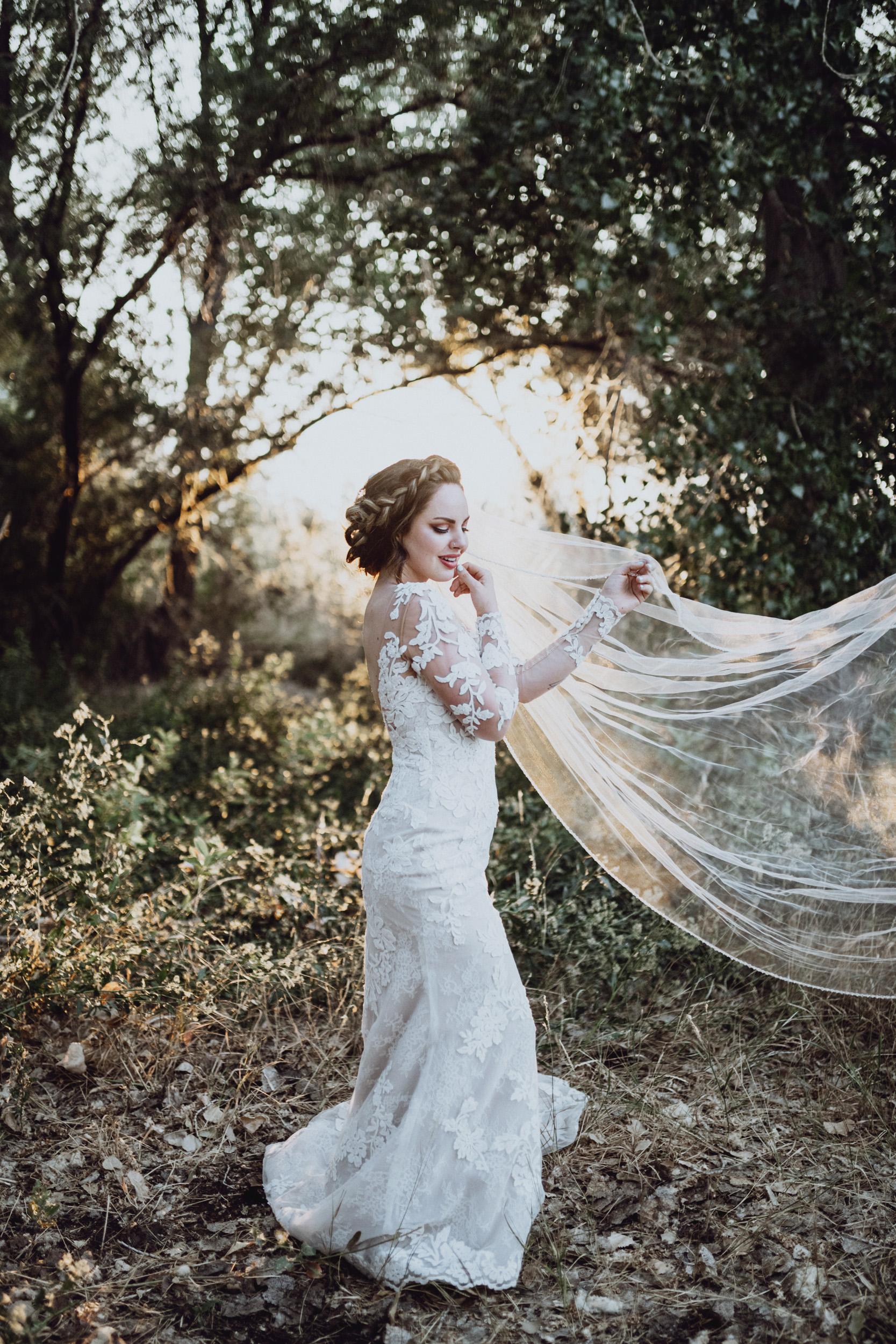 Bride in lace dress standing in grassy field