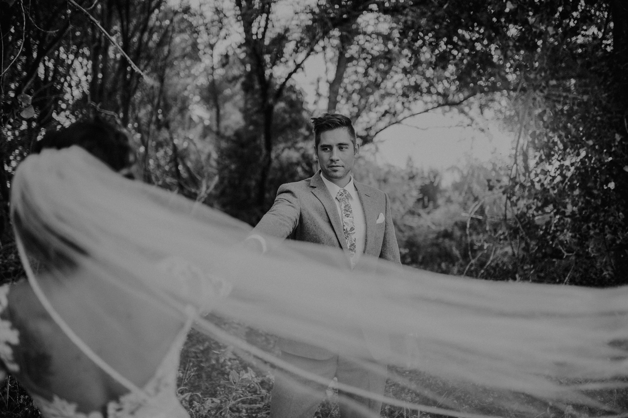 Groom looking at bride with a vail in a grassy field