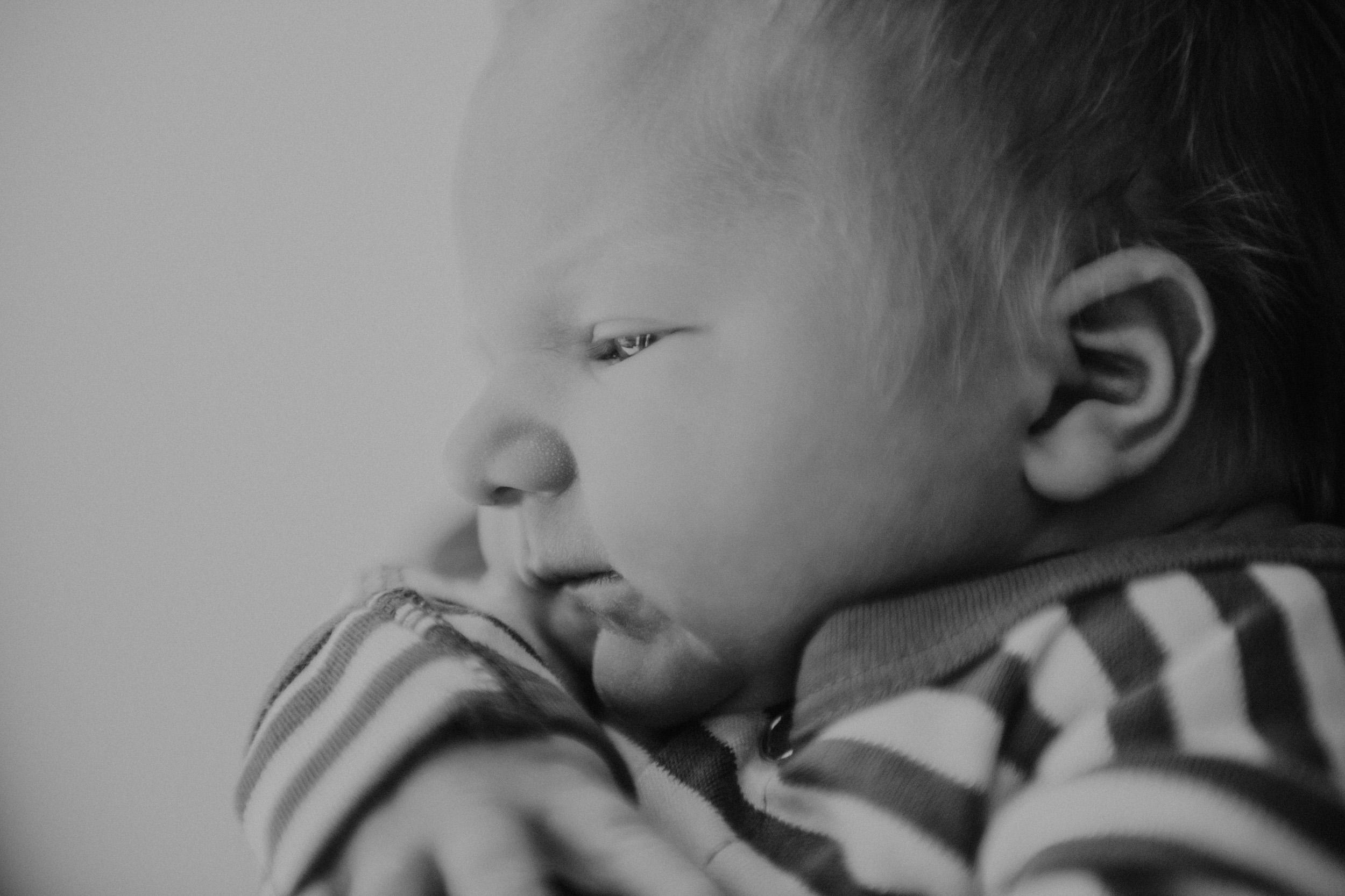 newborn boy in striped onesie being held by mom