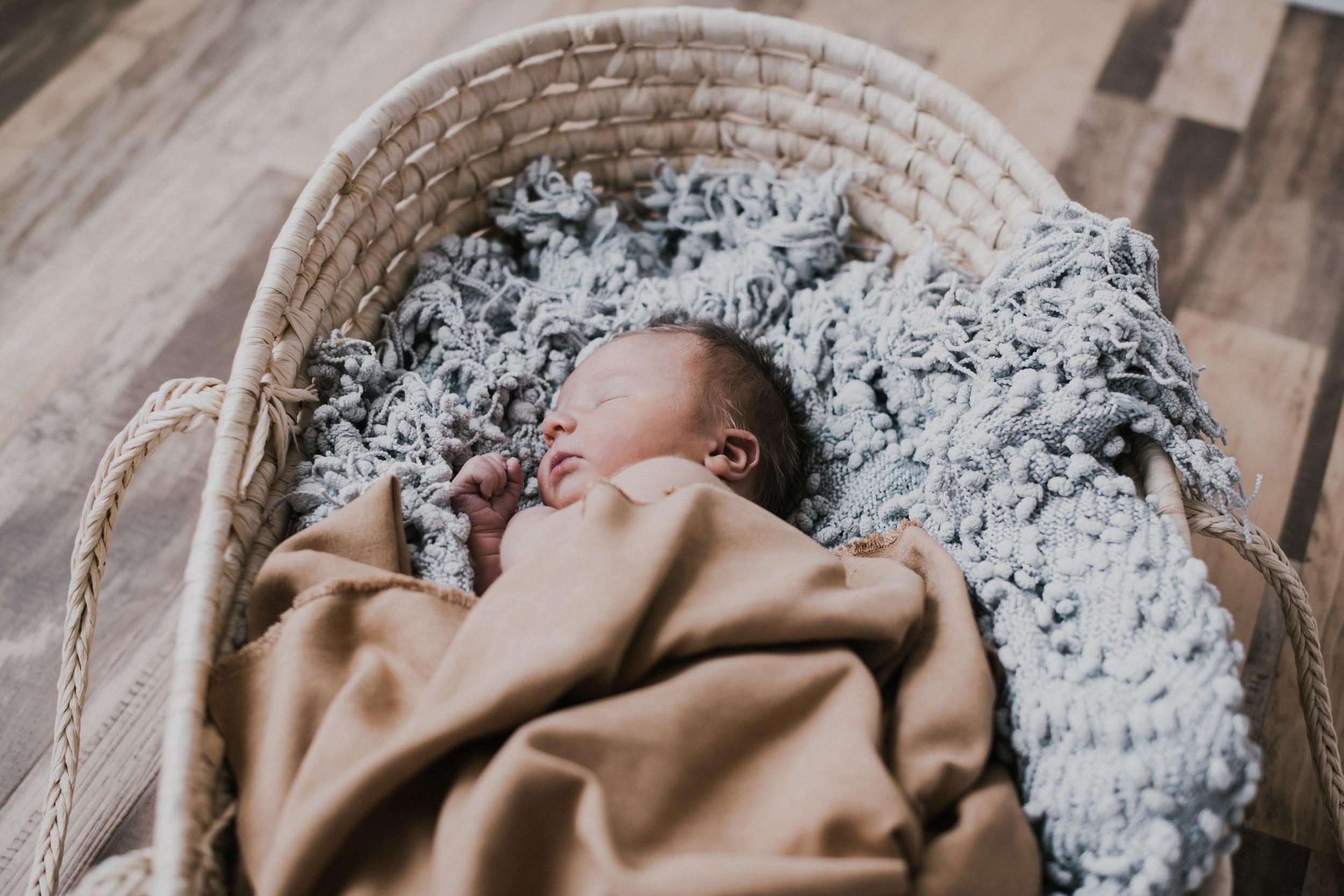 newborn baby boy sleeping in moses basket