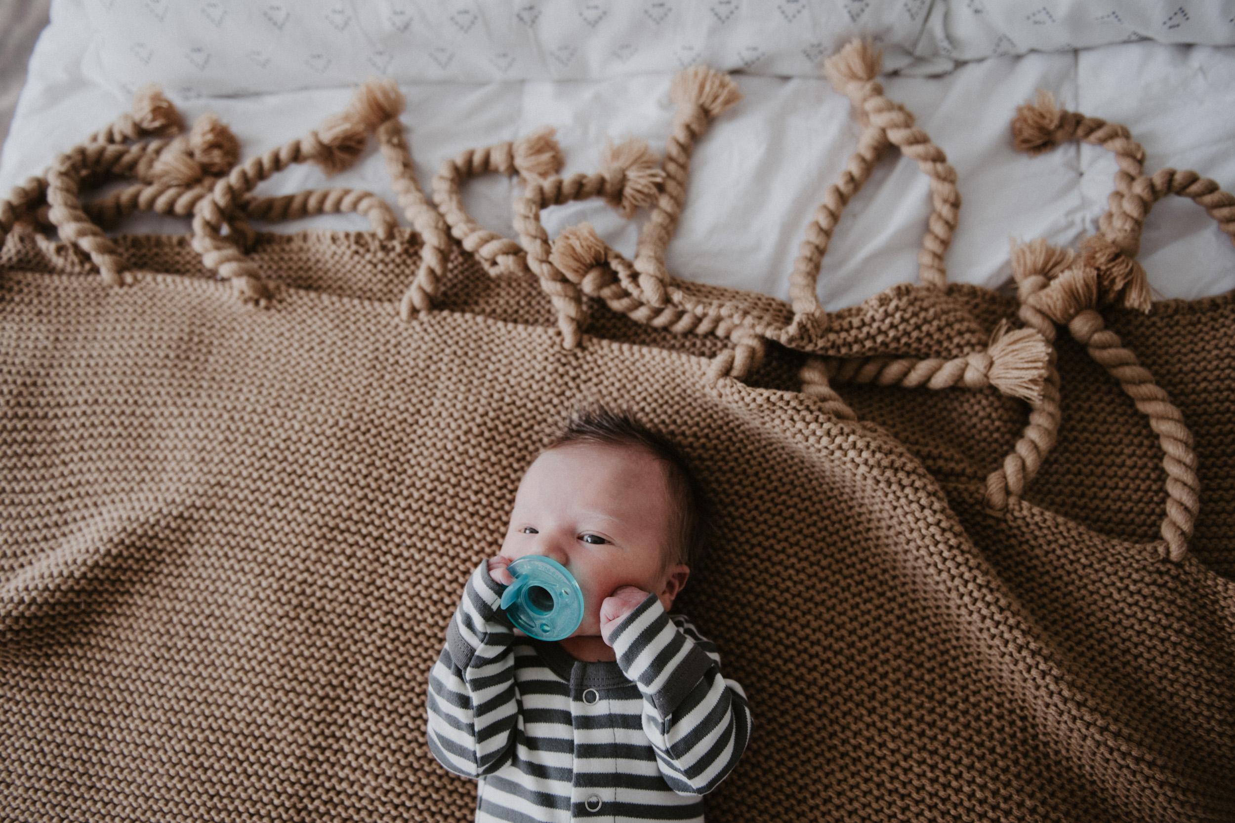 newborn in striped onesie on brown blanket with binkie
