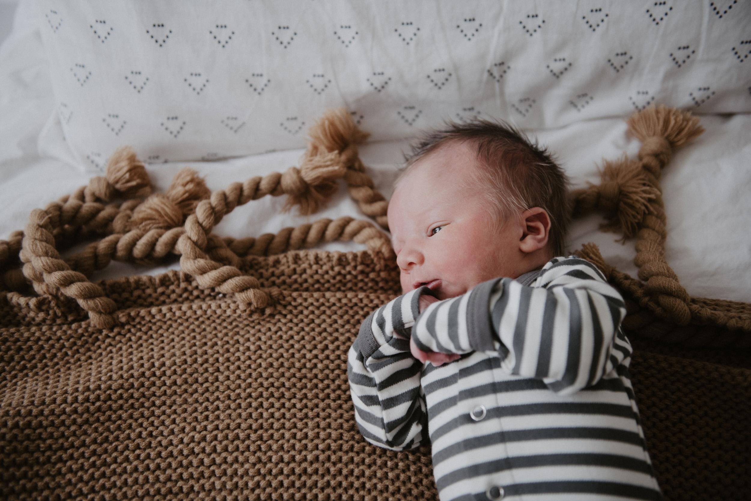 newborn in striped onesie on brown blanket
