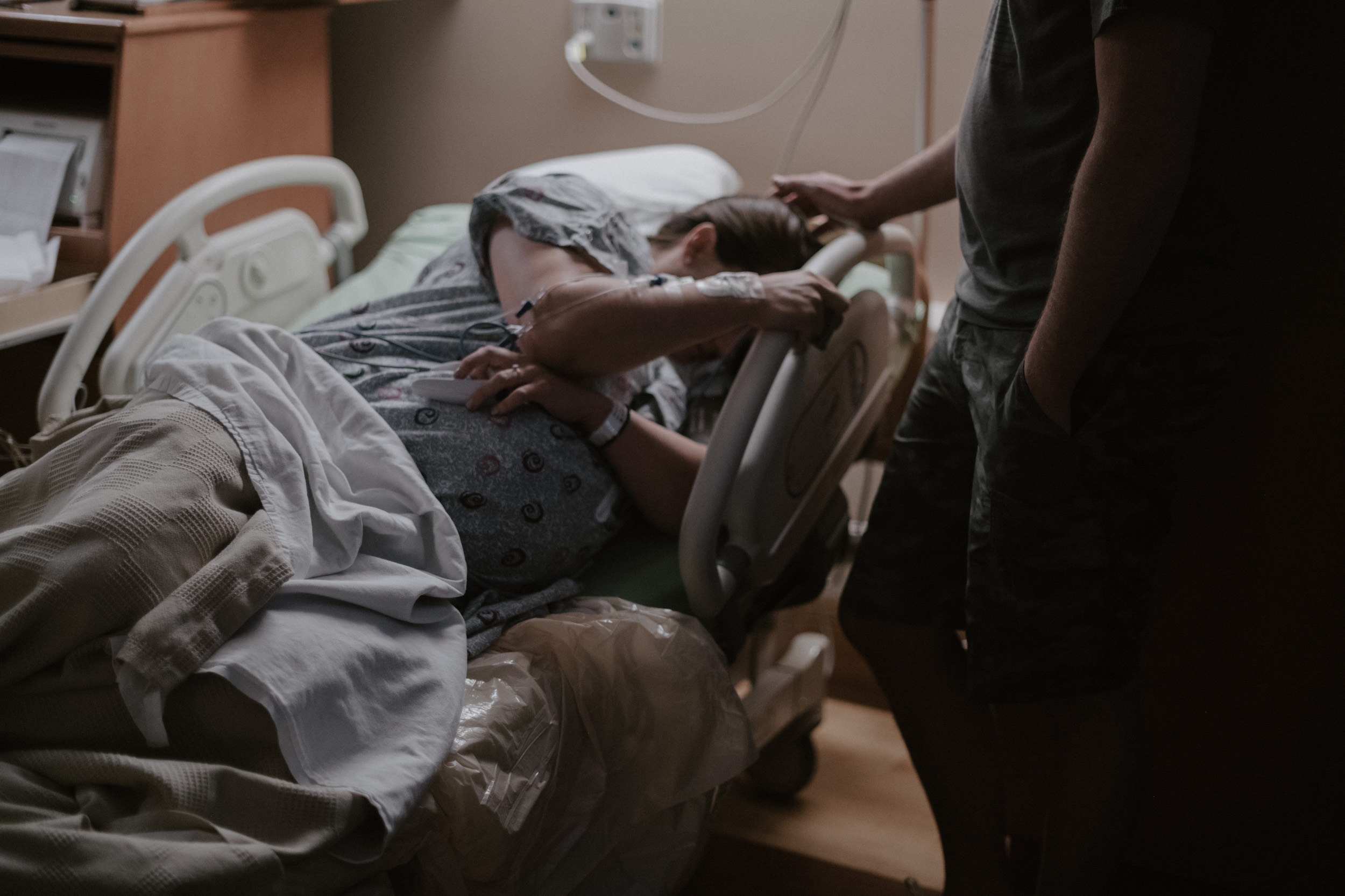dad standing next to mom in labor and delivery bed