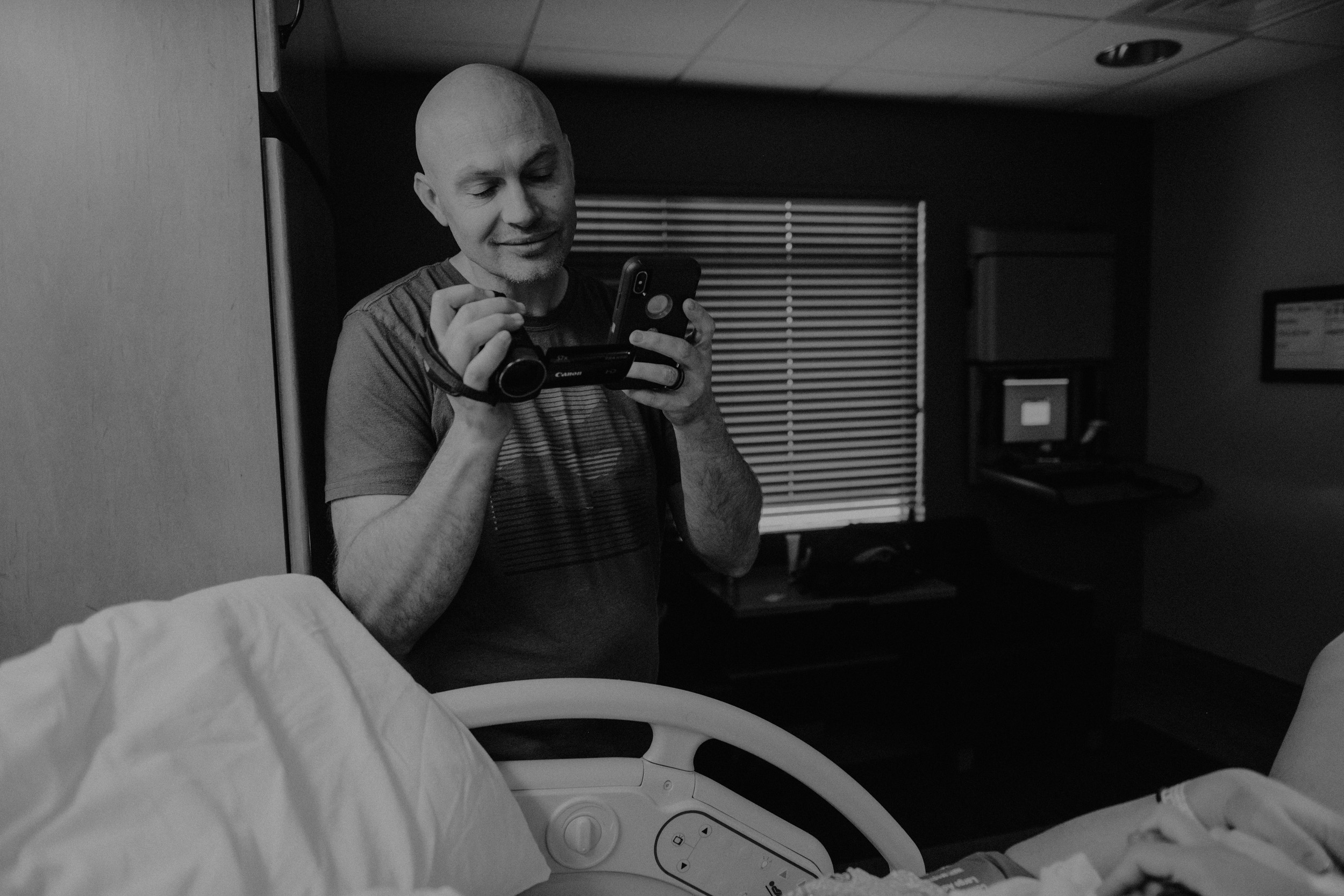 dad video recording baby being born