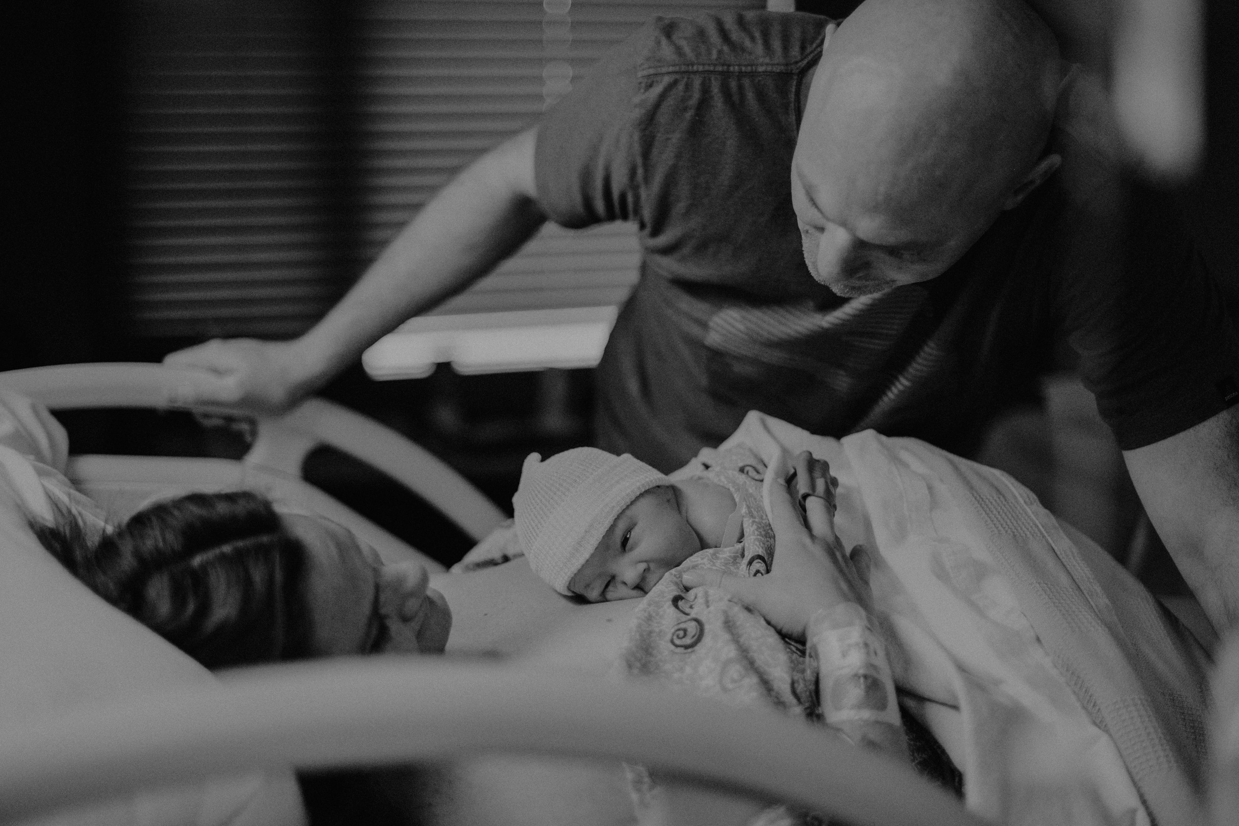 baby lying skin to skin on mom's chest after delivery dad looking at baby