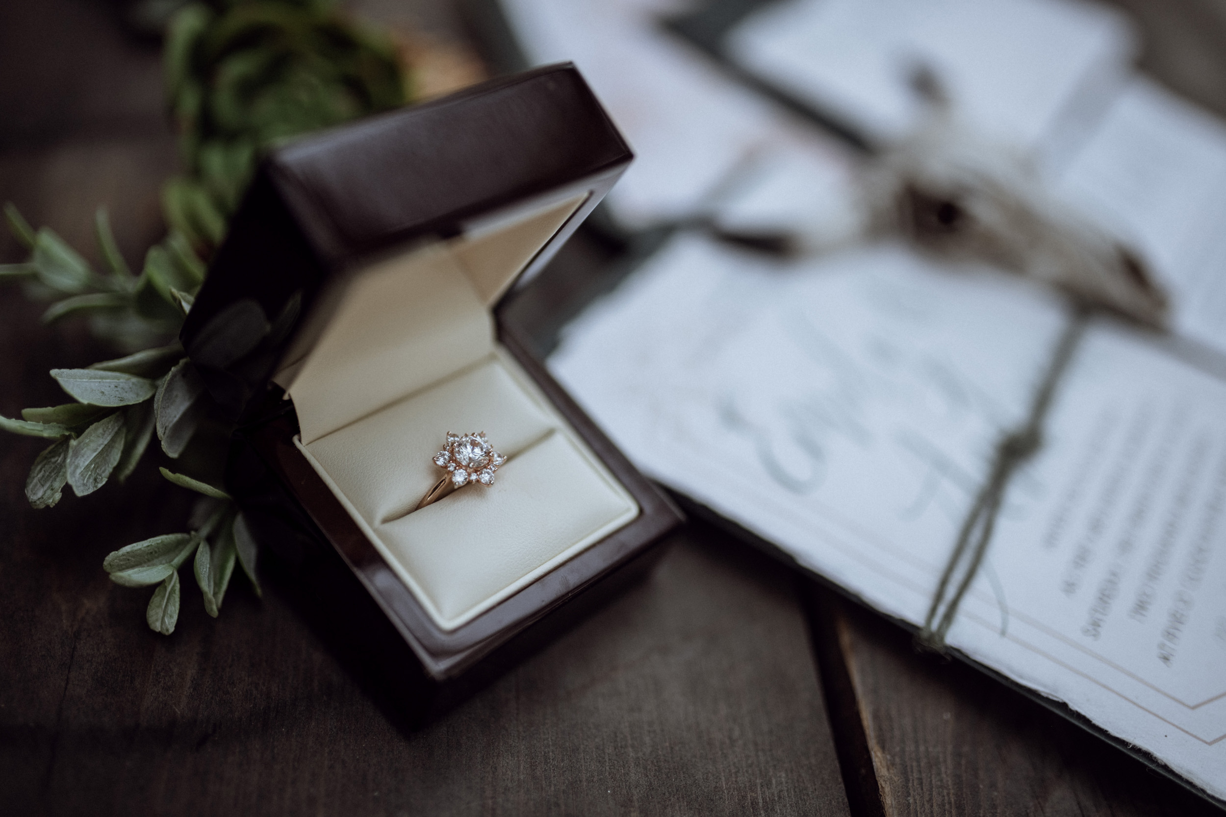 rose gold wedding ring on wooden table with stationary