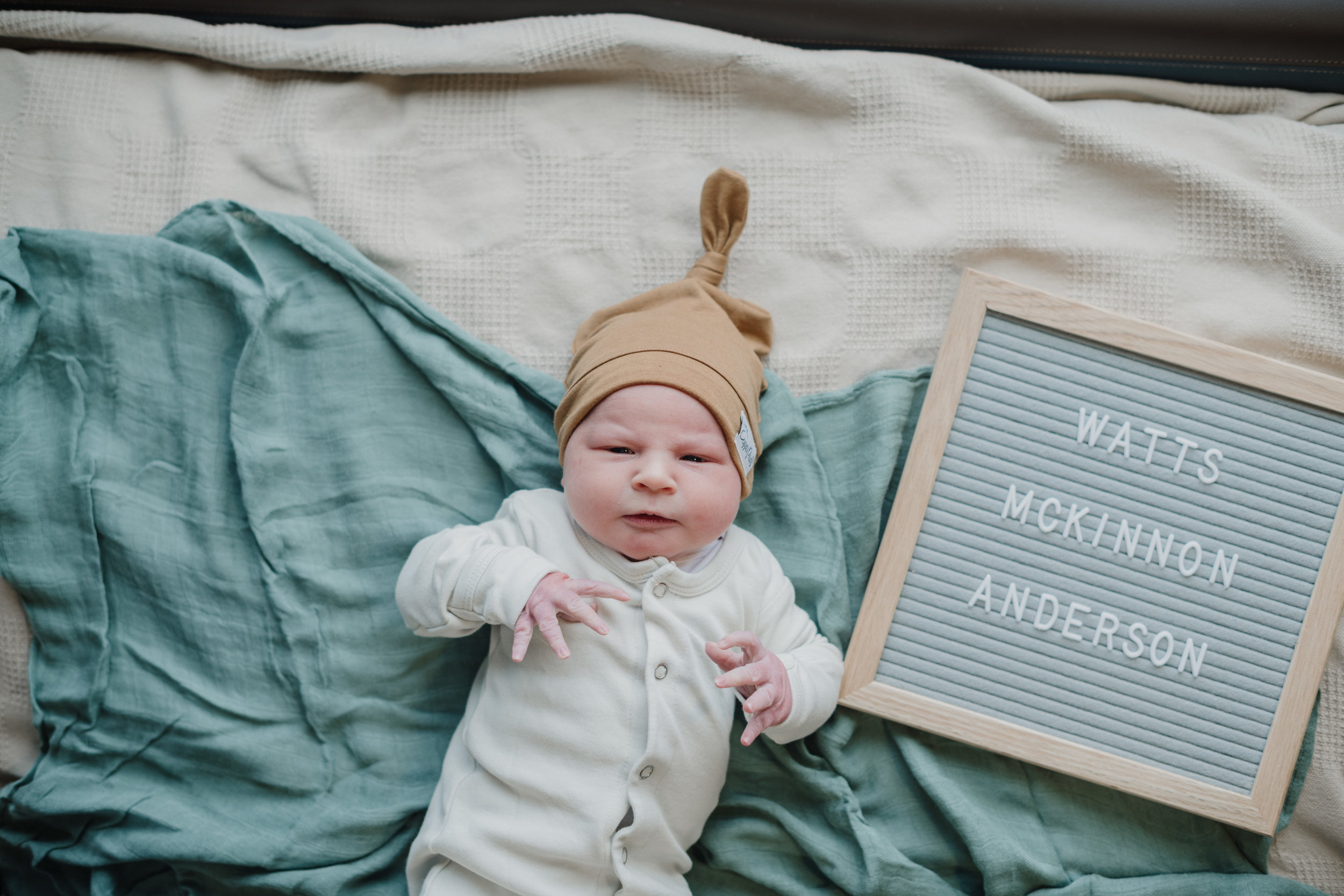 newborn baby with name on letter board