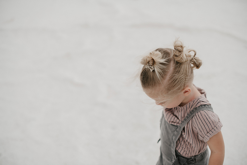 toddler in overalls with buns in hair walking on bonneville salt flats